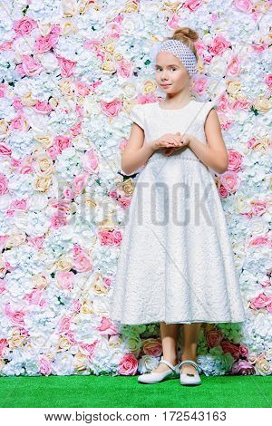 Cute smiling girl in beautiful white dress standing by a floral background. Spring and summer inspiration. Kid's fashion. Full length portrait.