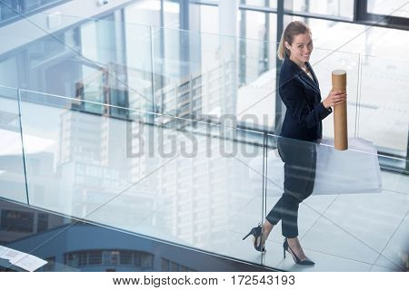 Beautiful cityscape against clear sky against businesswoman standing at office corridor with chart holder