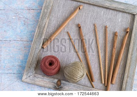 The composition on the theme of knitting. A set of hooks of different sizes and balls of cotton yarn in old wooden frame.