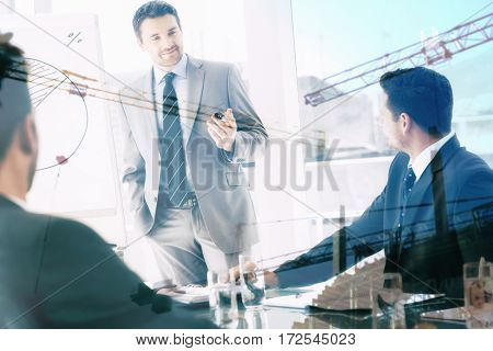 Crane and building construction site against business people in office at presentation