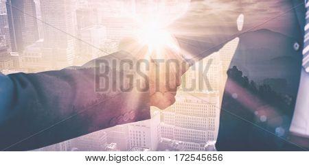 Businessmen shaking hands against sunrise over mountains