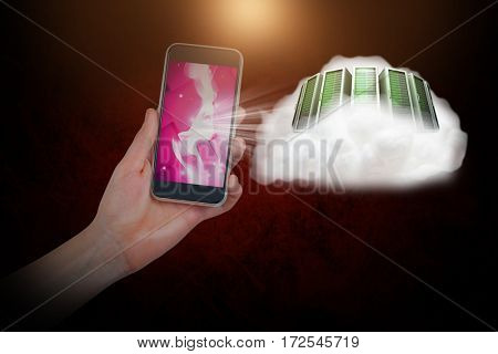 Hand holding mobile phone against dark background