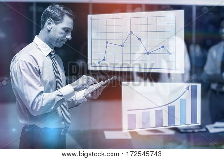 Graph against businessman using digital tablet