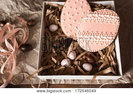 Egg form sweets in gift box close up. Cookies with pink glaze and chocolate eggs in package, traditional Easter treat. Confectionery, homemade pastry, seasonal, surprise concept