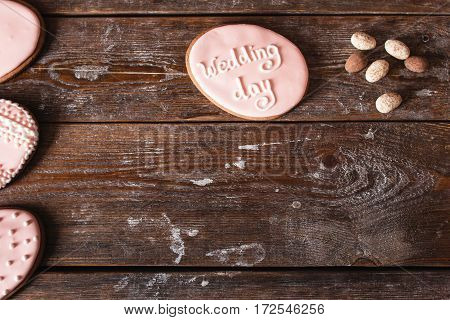 Cookie with wedding day sign on wood free space. Original invitation for marriage party on wooden table, flat lay. Bakery, dessert, cake concept