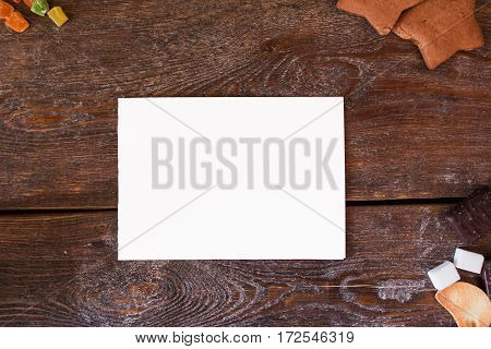 Blank card on wooden background with cookies free space. Top view on wooden table with white empty sheet of paper and sweet pastry, free space for text