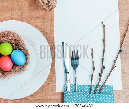 Festive table and colorful Easter eggs in a plate