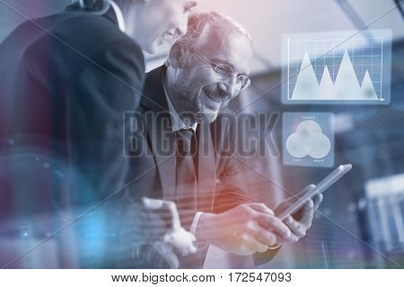 Graph against businessman with colleague using digital tablet