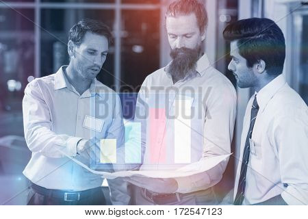 Graph against businessmen discussing over blueprint