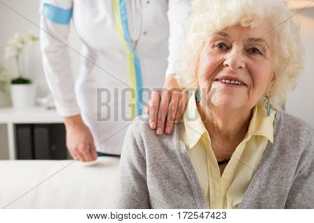 Nurse holding hand on elderly womans shoulder