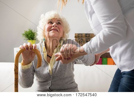 Nurse helping elderly woman to get up