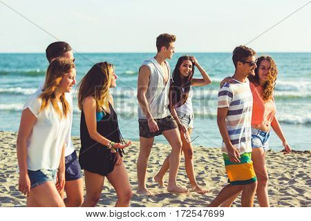 Multiracial Group Of Friends Walking On The Beach