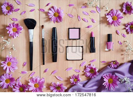 Set makeup decorative cosmetics in shades of purple on a wooden background decorated with spring flowers. Blush, powder, eye shadow, makeup brushes, nail polish. Flat lay. Top view.