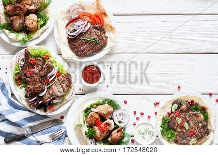 Grilled meat meals on table flat lay. Top view on assortment of tasty bbq snacks, free space on white wooden background. Restaurant menu, buffet, lunch concept