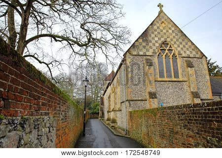 WINCHESTER, UK: A walkway with colorful walls leading to a church located on St Michaels Passage