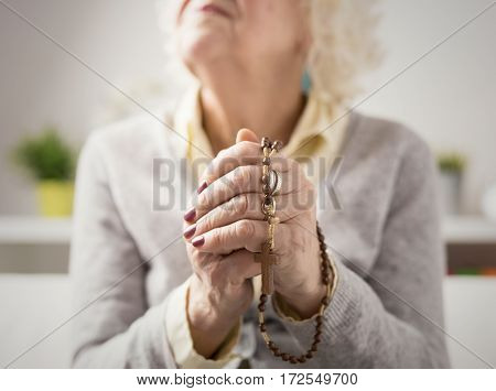 Grandma prayng with rosary in her hands