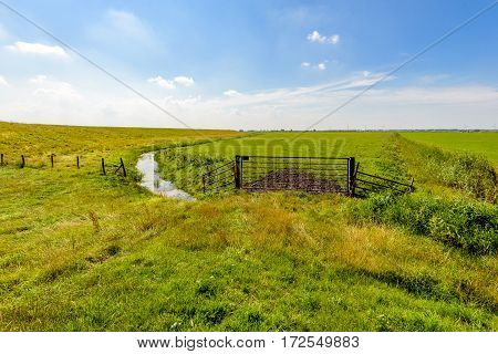 Dike ditch and a rusty gate in a typical Dutch polder landscape in the summer season.