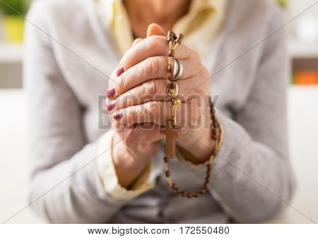 Grandma holding wooden rosary in hands and praying