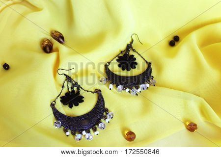 handmade accessories earrings with black flowers on the yellow background