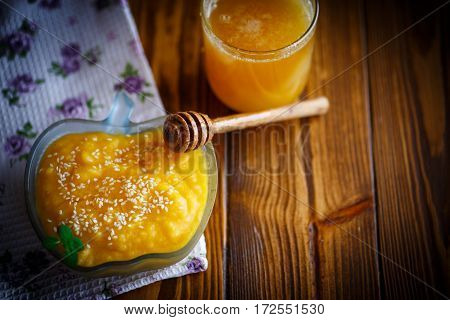 sweet pumpkin porridge with honey and sesame seeds on a dark table