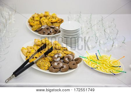 yellow cookies on a white plate next to a lemon