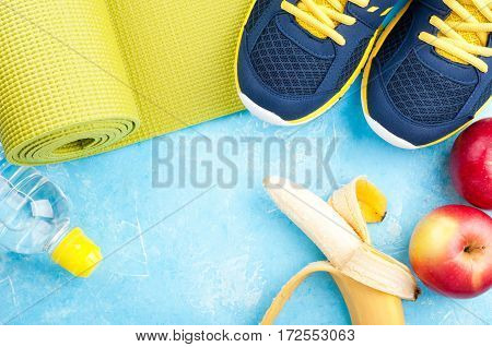 Yoga mat sport shoes apples banana bottle of water on dark background. Concept healthy lifestyle healthy eating sport and diet. Sport equipment. Copy space
