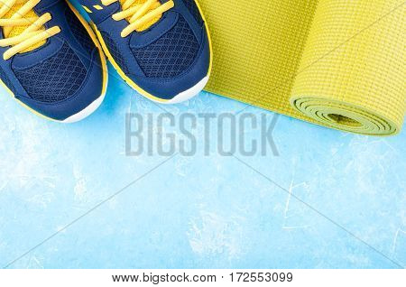 Yoga mat and sport shoes on blue background. Concept healthy lifestyle sport and diet. Sport equipment. Copy space