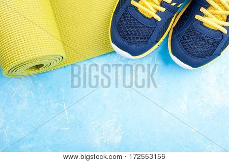 Sport and healthy lifestyle concept. Yoga mat and sport shoes on light background. Sport equipment. Copy space