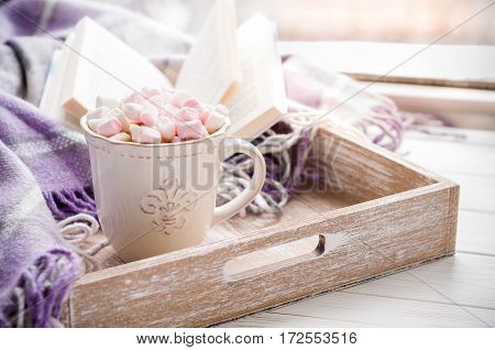 Coffee cup open book marshmallow and plaid on a window sill in winter. Concept warm and cozy home breakfast