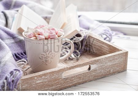 Breakfast. Coffee cup open book marshmallow and plaid on a window sill in winter. Concept warm and cozy home decor