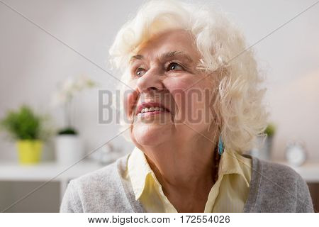 Portrait of happy elderly woman daydreaming and smiling