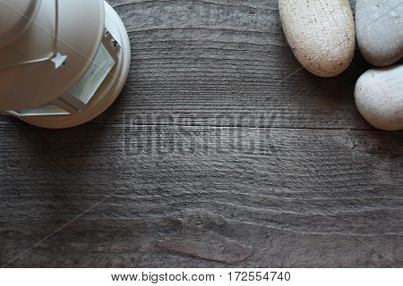Dark wooden background with stones and white lantern