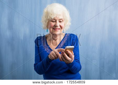 An elderly woman using smartphone and smiling