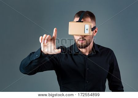 Man using a new virtual reality headset on grey background. Men's emotions