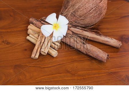 Whole coconut, cinnamon sticks and flower on wooden brown table. Close-up