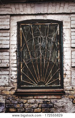 broken window in an abandoned old building made of bricks