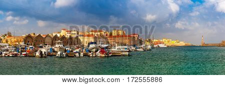Panorama of Chania Arsenals, the Venetian shipyards, and fishing boats in old harbour of Chania in sunny and cloudy summer morning, Crete, Greece