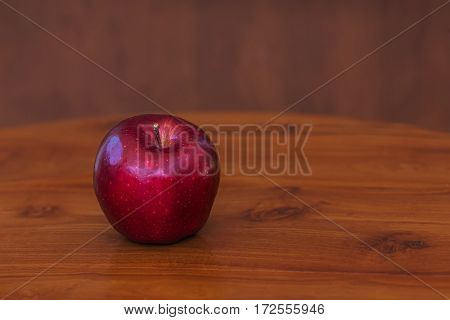 Red juisy apple on a brown wooden table and brown background. Close-up