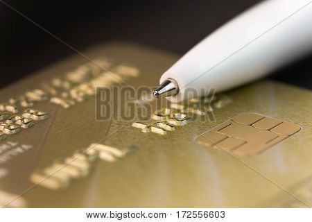 fragment of a gold credit card and ballpoint pen closeup