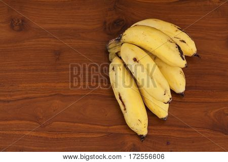 Very fresh yellow banana bunch on brown wooden table. Close-up