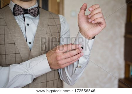 Man buttoning on the sleeve of his shirt. Zip up the cufflink. Men's style. Professions. The groom in a bow tie. Going to work to the meeting.