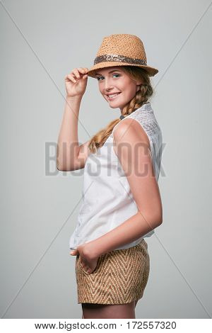 Beautiful smiling woman wearing summer straw fedora hat looking at camera over shoulder holding hat brim
