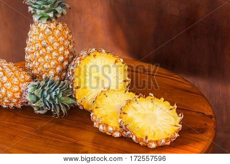 Two whole and some cutting slices pineapples on brown wooden table. Close-up