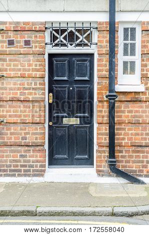 entrance from outside to a brick building a stylish black door interesting window and black gutter urban architecture