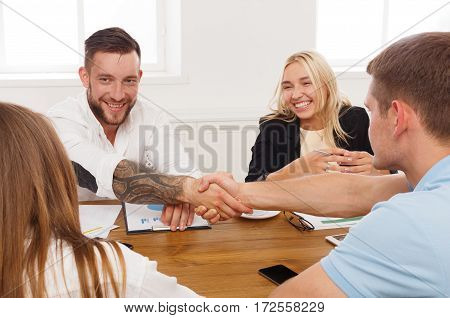 Business handshake at office corporate meeting, contract conclusion and successful agreement concept. Modern hipster businessman and other man's hands meet