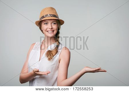 Smiling woman in summer straw hat showing open hand palm with copy space for product or text over grey background