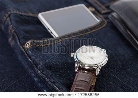Wrist Watch And Smartphone On Denim Jeans