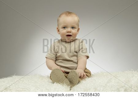 Adorable 9 month baby boy on the white blanket on grey background. Studio shot