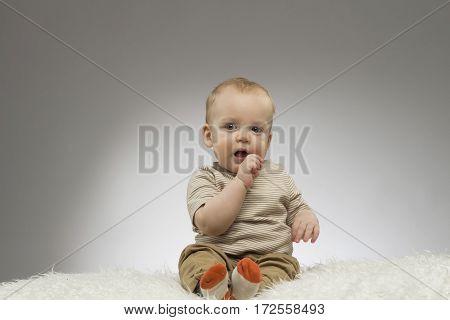 Cute baby boy sitting on the white blanket on the grey background. Studio shot
