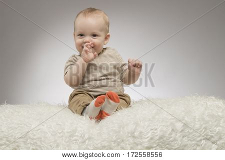 Funny little baby boy with fingers in the mouth, sitting on the white blanket, studio shot, isolated on grey background.